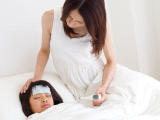 眠る子供を体温計を持って見つめる母親