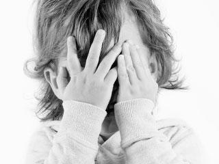 顔を両手で覆う子供