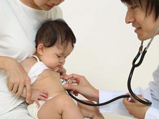 乳児の胸に聴診器を当てる医者