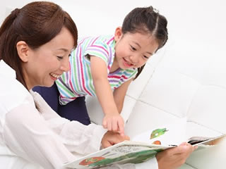 子供に絵本を読み聞かせる母親