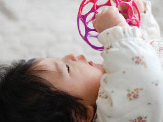 玩具を手で掴む赤ちゃん