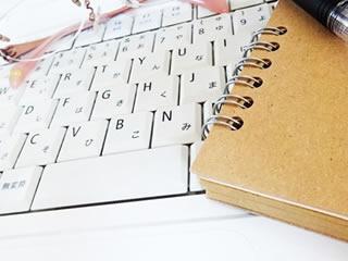 家計管理に使うパソコンのキーボードとノート