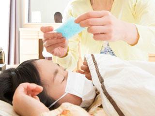 寝る子供の額に熱さましシートを貼る母親