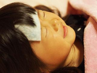 熱冷ましシートを額に貼って寝る女の子
