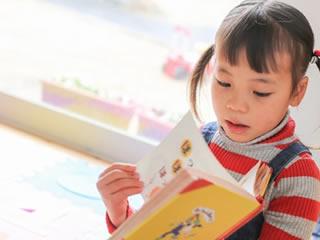 幼稚園で絵本を読むツインテールの女の子