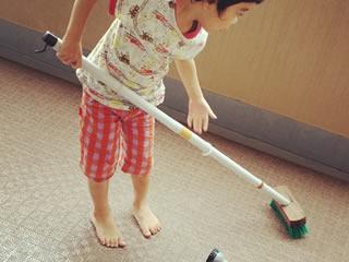 母親の手伝いで床を磨く男の子