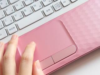 ピンクのパソコンで家計簿を付ける女性