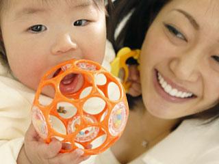 ガラガラを口につける赤ちゃん