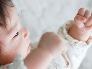 自分の手を見つめる赤ちゃん