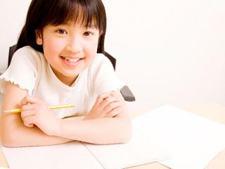 鉛筆を持って机に向かう子供