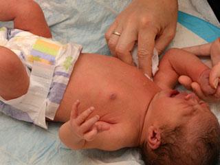 赤ちゃんの体をガーゼで拭く