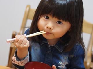 再婚相手と食事するシングルマザーの子供