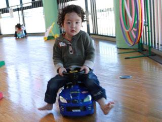 玩具の車に乗る子供