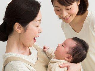 赤ちゃんを抱く祖母と見守る母親