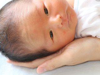 赤ちゃんの耳に手を添える母親