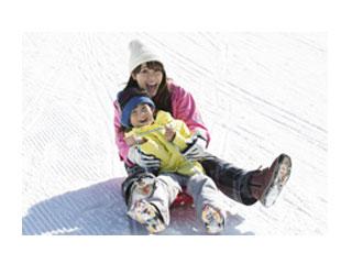 子供を膝に乗せてソリで滑る