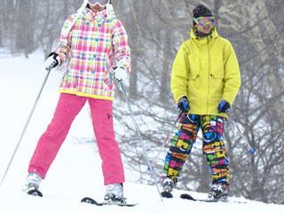 スキーで斜面を降りる二人