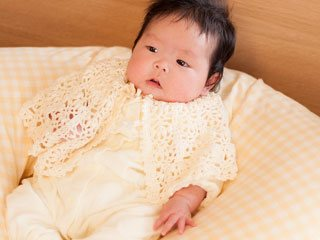 クッションに横になる新生児