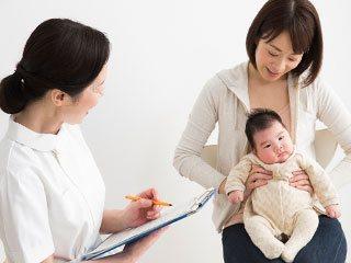 赤ちゃんを医師に診せる母親