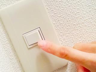 電気代節約の為に電源スイッチをOFFにする女性