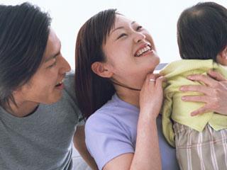 赤ちゃんをあやす母親と傍で見守る父親