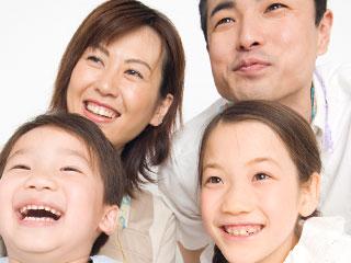 父母と兄弟が正面を見て笑顔