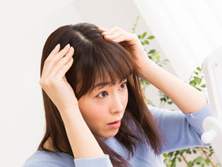 髪の分け目を鏡で見つめる女性