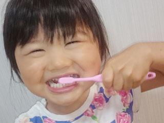 左手で歯磨きする子供
