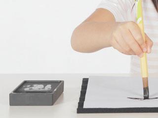 半紙に筆で文字を書く子供