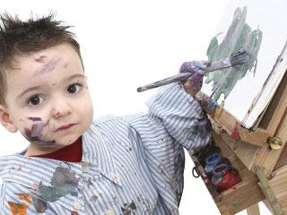 左手で絵筆を持ってキャンバスに向かう子供