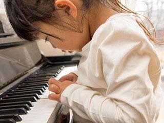 ピアノの鍵盤を指先で押す女の子
