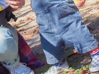 冬の公園で遊ぶデニムを着た親子