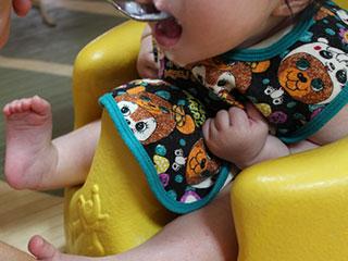 ベビーチェアに座って食事をとる赤ちゃん