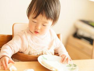 補助椅子に座り食事する赤ちゃん