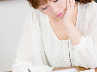 マイナンバーカード申請書に必要事項を記入する女性