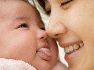 赤ちゃんに顔を寄せて笑う母親