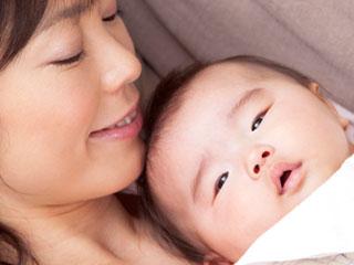 抱いた赤ちゃんを見つめる母親