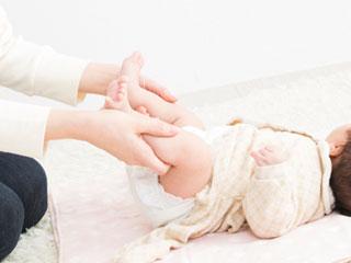 赤ちゃんのオムツを変える母親