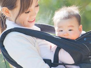 赤ちゃんを抱っこして外を歩く母親