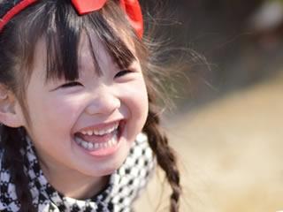 冬の公園で笑顔で走り回るシングルマザーの子供