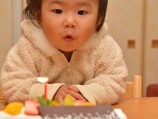 一歳誕生日のケーキの蝋燭を消す赤ちゃん