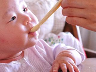 スプーンで粥を飲む赤ちゃん