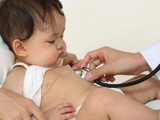お腹に聴診器を当てられる赤ちゃん