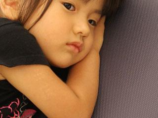 腕枕で見つめる子供