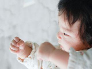 自分の手をじっと見つめる赤ちゃん