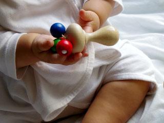 木でできたおもちゃを持っている新生児