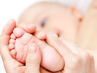 赤ちゃんの足の裏を指で押す