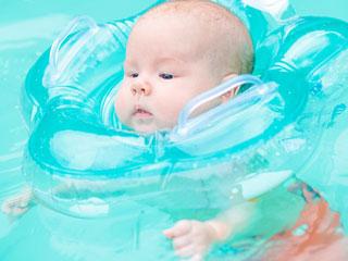 浮き袋をつけてプールに浮かぶ赤ちゃん
