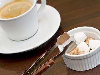 喫茶店のコーヒーとオシャレな容器に入れられた角砂糖