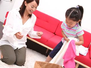 衣類を整理する子供の横で口出しする母親